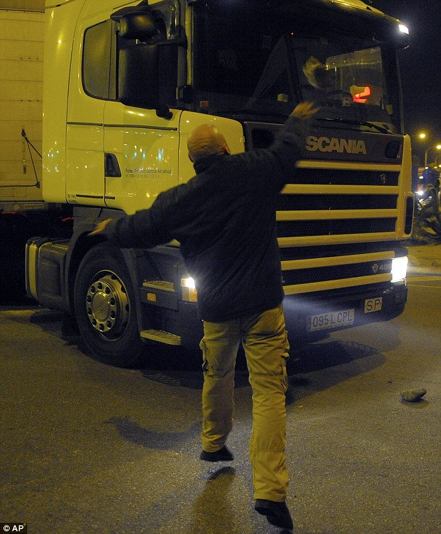 Fury: A protestor hurls a stone at a truck in Barcelona. The General Workers Union said the stoppage, the second this year, was being heeded by nearly 100 per cent of workers in the automobile, energy, shipbuilding and constructions industries