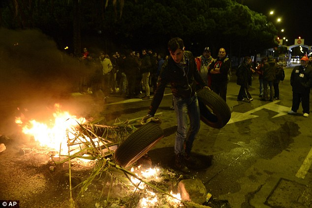 Protesters burn tyres at the main entrance to Mercabarna, the biggest wholesale market in Barcelona. Similar work stoppages are taking place in Portugal and Greece, to protest government-imposed austerity measures and labor reforms