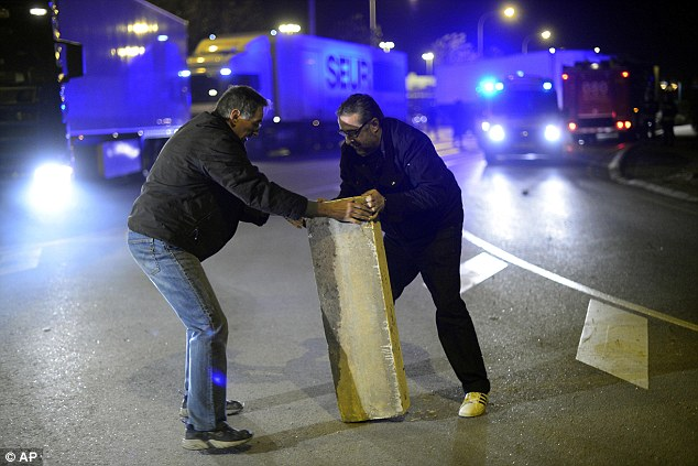 Protesters move a concrete block shut off the main entrance to Mercabarna, the biggest wholesale market in Spain in Barcelona