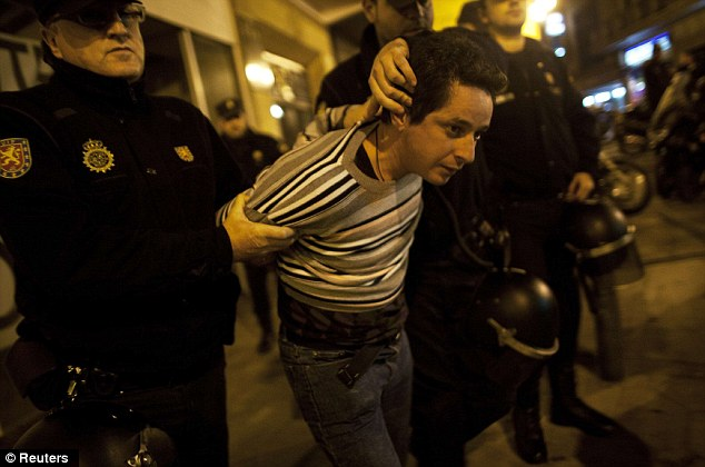 Arrest: A protester is hauled away by riot police officers after trying to close a bar as part of strike action in Malaga, southern Spain in the early hours of the morning