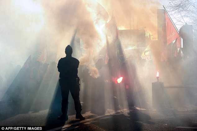 Haze: A police officer watches a man brandishing a flare during an anti-austerity protest in Lille in northern France