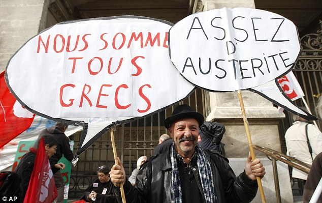 A French worker holds placards reading 'We are all Greek, enough austerity', during a demonstration in Marseille