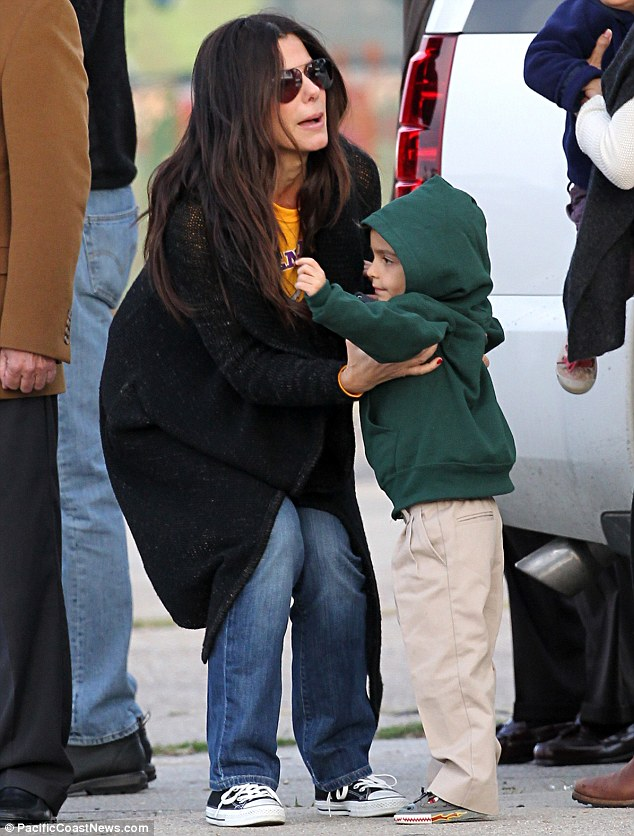 Helping hand: Sandra picks up Camila and Matthew's son while at the performance