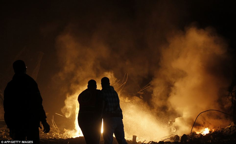 Palestinians try to extinguish fire following an Israeli air strike on Gaza City