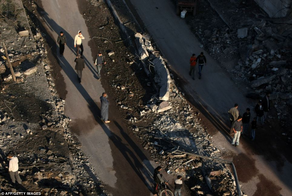 Destroyed: Palestinians inspect an area targeted by an Israeli air strike in Gaza City in the early hours of this morning
