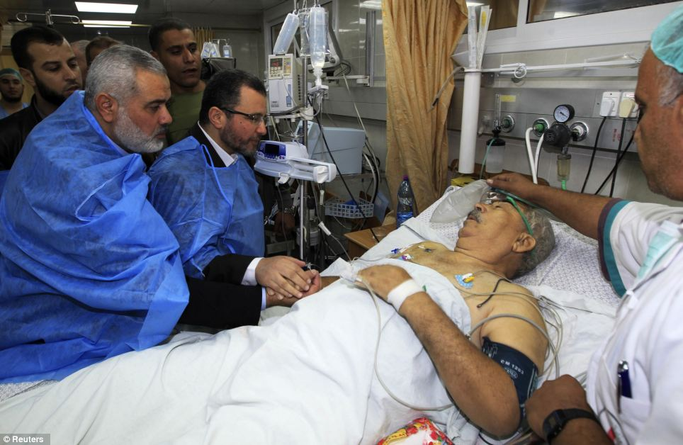 Support: Senior Hamas leader Ismail Haniyeh and Egypt's Prime Minister Hisham Kandil (far left) hold the hand of a patient, who was injured during an Israeli strike, during their visit to a hospital in Gaza City