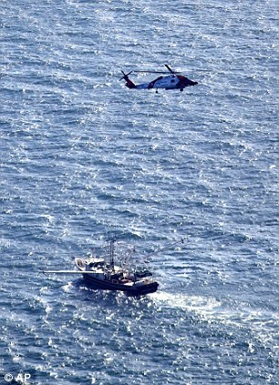 In this aerial photo, a Coast Guard helicopter flies over the area of an explosion and fire on an oil rig in the Gulf of Mexico, about 25 miles southeast of Grand Isle