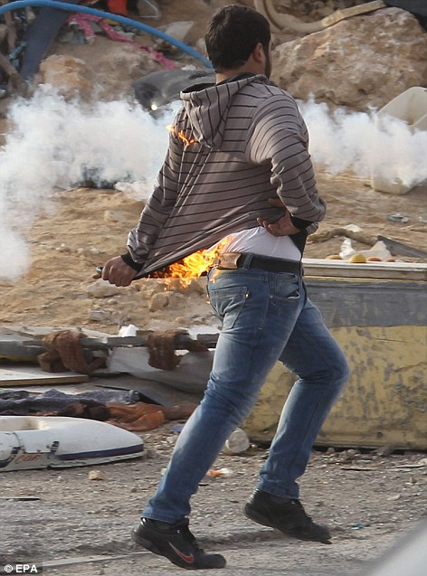 A Palestinian protester runs with his clothes on fire after trying to throw a Molotov cocktail at Israeli troops near the West Bank city of Ramallah