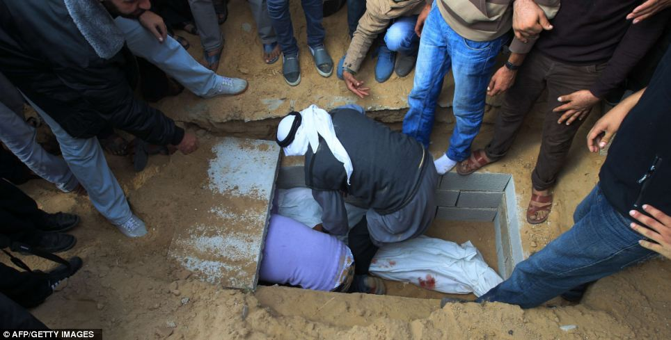 Palestinian mourners bury the body of Hamas militant Shadi al-Sheir during his funeral in Maghazi refugee camp in central Gaza Strip