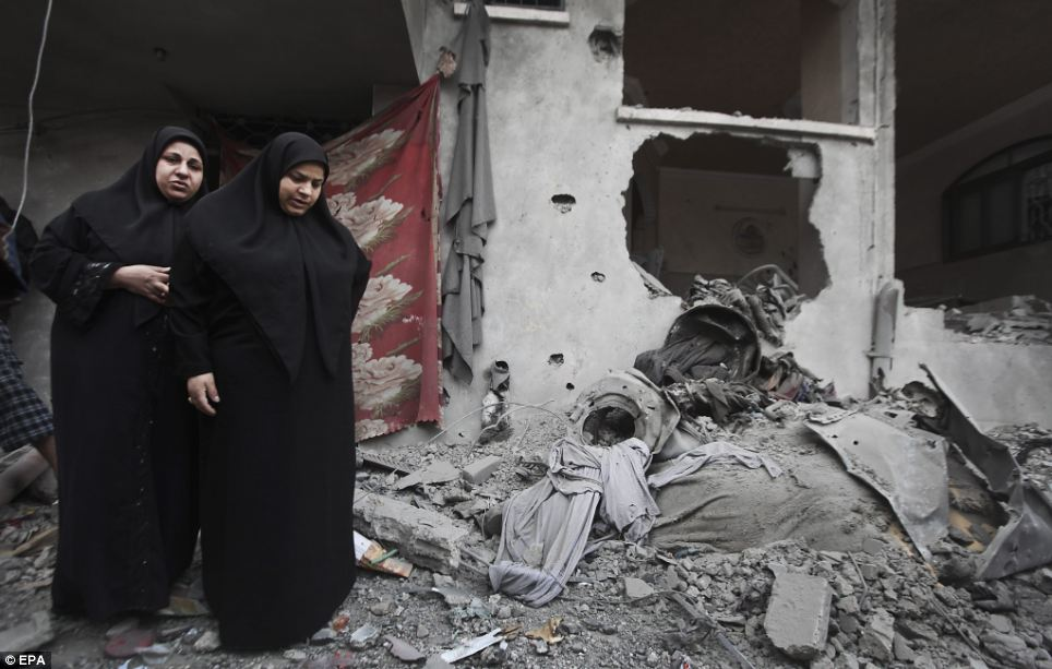Two Palestinian women view the rubble of their destroyed home after Israeli rockets hit the Hamas official house in Jabaliya refugee camp in the northern Gaza Strip