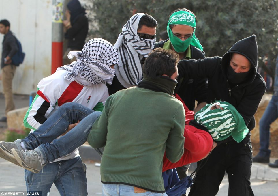 A student from the University of Birzeit is carried away injured during clashes with Israeli soldiers in the occupied West Bank town of Betunia