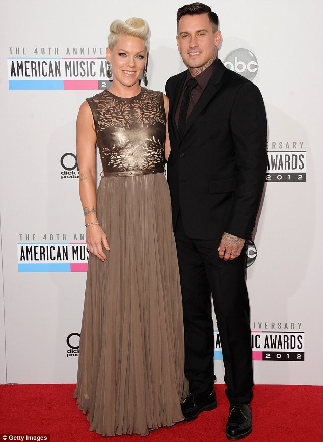Stand by your man: Pink wore a metallic gown with a leather cut-out top and full skirt as she posed up with husband Carey Hart