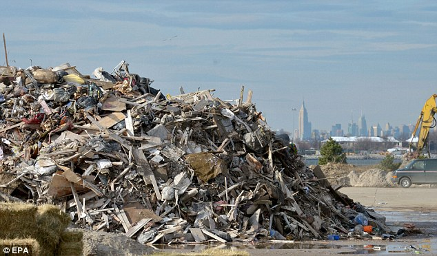 Little left: A pile of debris from damaged homes in Rockaway Park, where disabled David Gotthelf, 72, drowned in his own home after emergency services failed to respond
