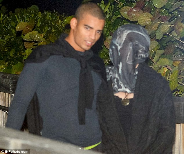 Hidden from view: Brahim was happy to leave himself uncovered but Madonna chose to hide away on their night out