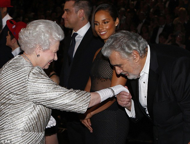 Charmer: Alicia Keys smiled as she watched Placido Domingo kiss the Queen's white glove on her right hand