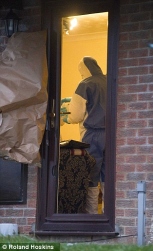 Evidence: A forensics officer is seen carrying bags out of the house