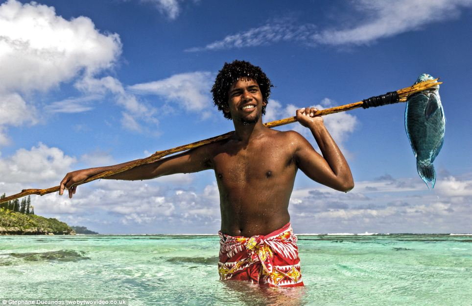 Albert shows off his spear and what he can catch on the island where people live almost entirely on fish and other sea creatures