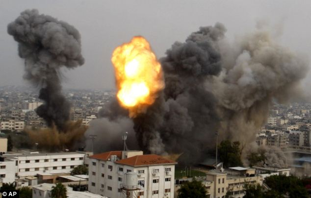 Smoke and a ball of fire are seen after an Israeli air strike in Gaza City. Israeli aircraft pounded Gaza with at least 30 strikes on Tuesday night