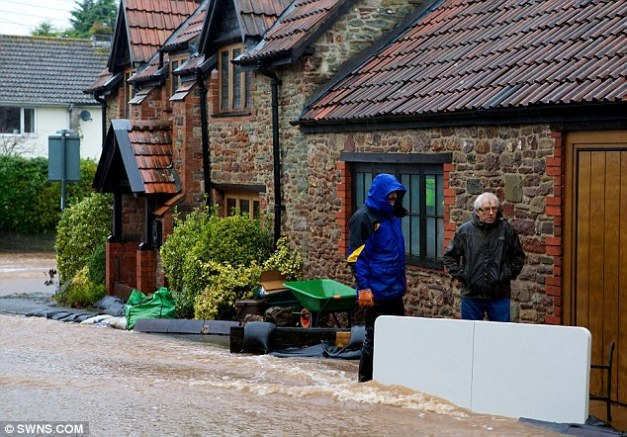 Mounting their defences: A homeowner laid out sandbags and a table in a bid to stop the torrent of water entering his home in Portbury, near Bristol on Wednesday