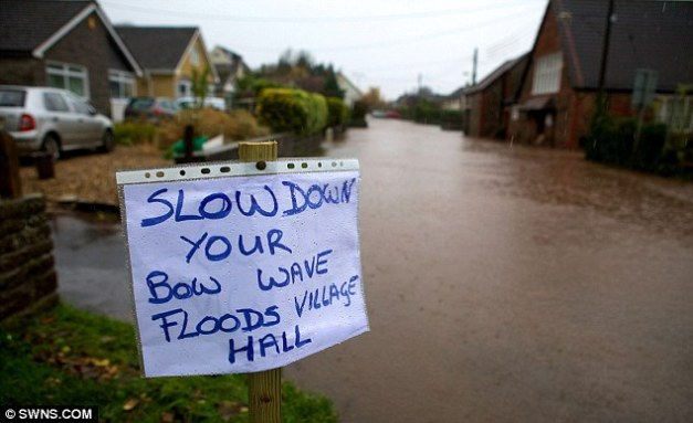 Go slow: Portbury residents put up a sign warning motorists to slow down if they go through the flooded street