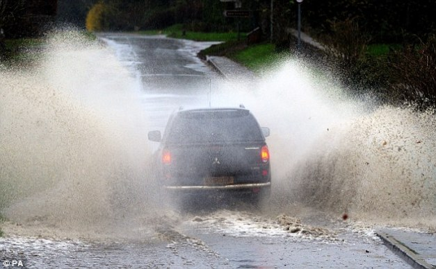 Water fountains: A 4x4 drives through floodwater in Coates, Gloucestershire, as motorists were urged to take greater care on Britain's roads on Wednesday after torrential overnight downpours