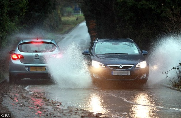 Splash: Two cars throw up fountains of water as they pass each other on Lapas Lane near Halesowen, West Midlands on Wednesday