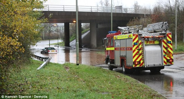 To the rescue: A fire engine draws up to help a stranded vehicle submerged in flood water in Ottery St Mary, Devon on Wednesday