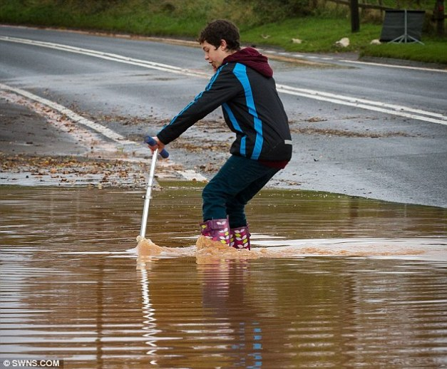 Water scooting: A young boy attemps to ride his scooter in flood waters outside Willowbrook Nursey & Garden Centre, near Taunton, Somerset, on Wednesday