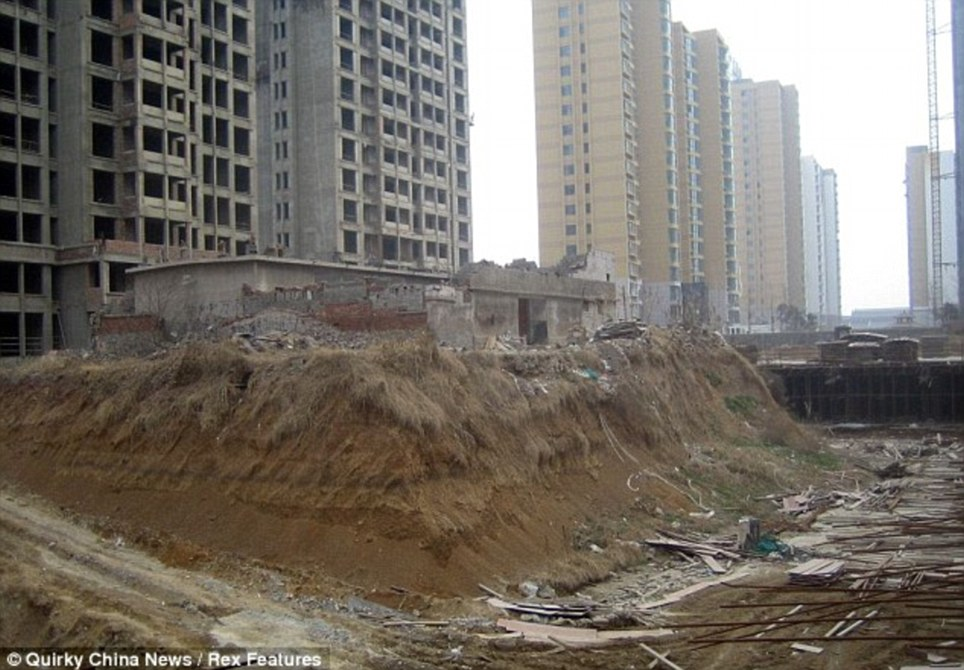 Stranded: The couple were left without running water and electricity ground after real estate developers dug out the ground around it