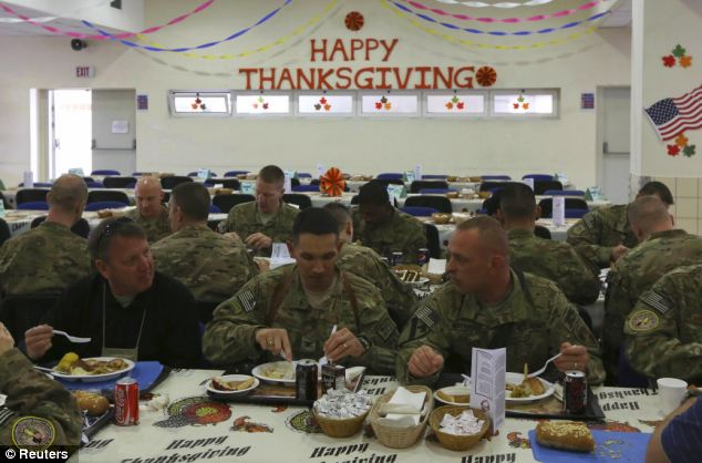 U.S. soldiers sit down to enjoy their Thanksgiving meal in Kabul