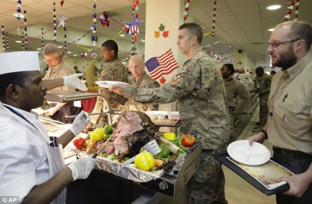 A feast for the forces: A dining facility worker, left, serves meat to soldiers and civilians for their Thanksgiving meal in Kabul
