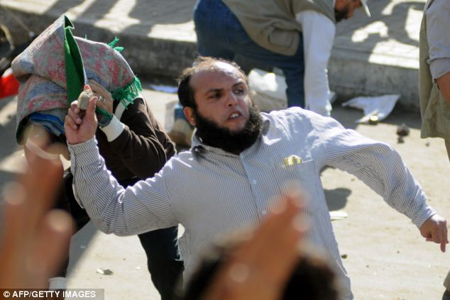 A man throws a stone at a rival rally the day after Morsi assumed the 'powers of a Pharaoh'