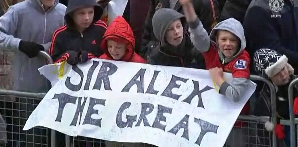 In support: United supporters braved the inclement weather at Old Trafford to see the new statue of Ferguson