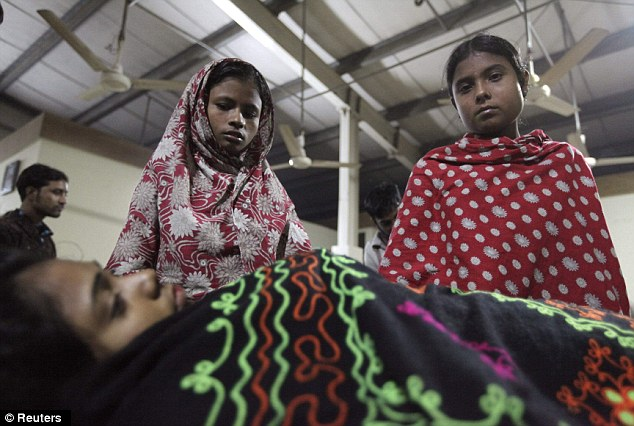 Hoping and praying: Colleagues stand beside Asma, a garment worker, who was injured in the devastating fire