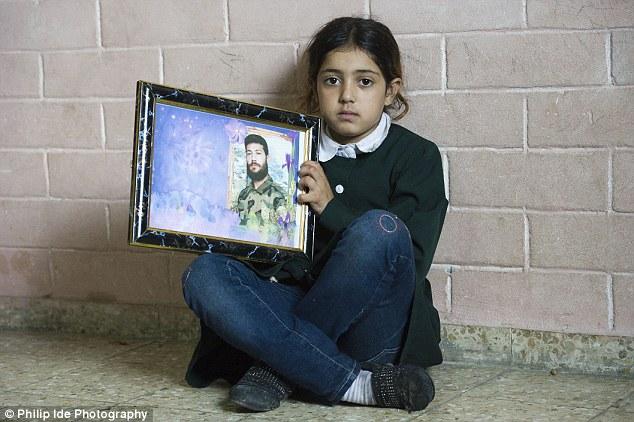 Aturdido: hija mayor del Sr. Badawi, Worood, que se traduce como Rose, con la foto de su padre