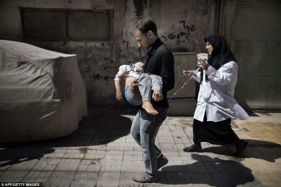 A Syrian man carries his wounded daughter outside a hospital in Aleppo in September