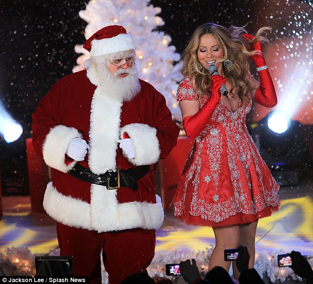 Naughty or nice? Mariah tossed her hair as Santa looked on
