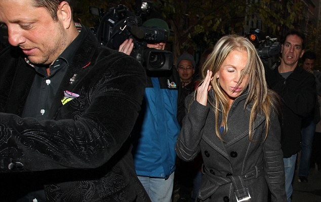 Battered: One of Lindsay Lohan's alleged victims seen leaving a Manhattan police station with a man believed to be her husband