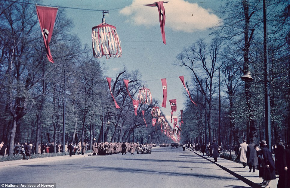 Force: In this picture we see military personnel father beneath decorations. An officer appears to be inspecting the men