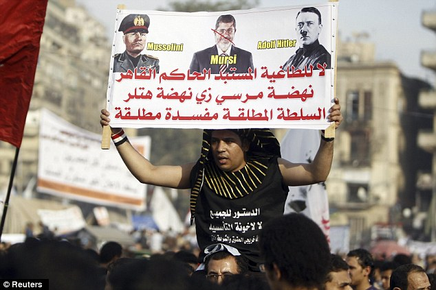 A protester in a Pharaoh headdress holds up a placard reading 'no to a dictator' during a demonstration on Tahrir Squareon Friday