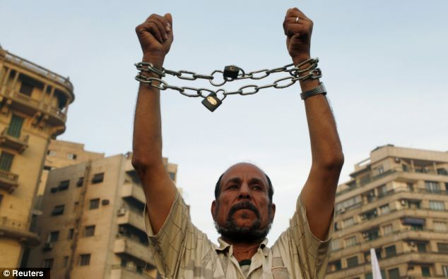 Imprisonment: An anti-Morsi protester chains his hands during yesterday's demonstrations, to symbolise the rule of the Muslim Brotherhood .he is likely to stay in chains when the muslim dictators throw him in prison as free speech is no more