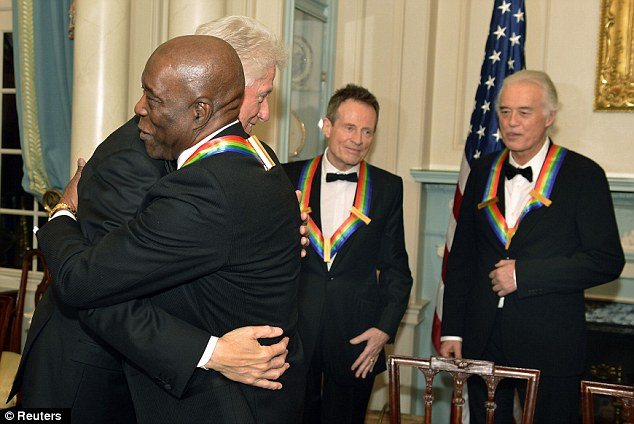 Friends: Former U.S. President Bill Clinton hugs Kennedy Center 2012 Honoree, Blues legend Buddy Guy as rock band Led Zeppelin members John Paul Jones and Jimmy Page watch in background