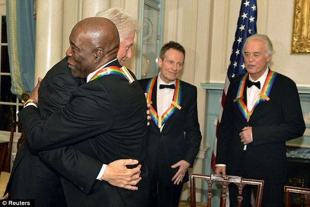 Friends: Former U.S. President Bill Clinton hugs Kennedy Center 2012 Honoree, Blues legend Buddy Guy as rock band Led Zeppelin members John Paul Jones and Jimmy Page watch in background