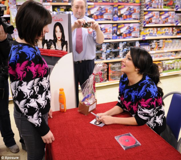 Who wore it best? Tulisa Contostavlos is greeted by a fan wearing the same Bank jumper as her at album signing in Birmingham