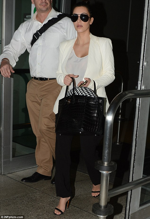 Low key: Kim was dressed down for once in a conservative pair of black trousers and white blazer for her 18-hour flight