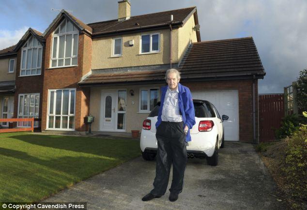 Farklı yaşamlar: Chris Dennis Anglesey'deki dört odalı evinin önünde.