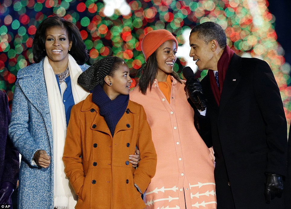 All together at Christmas: President Obama was joined by his wife and daughters, Sasha, second from left, and Malia, second right; the first family tonight lit the National Christmas Tree