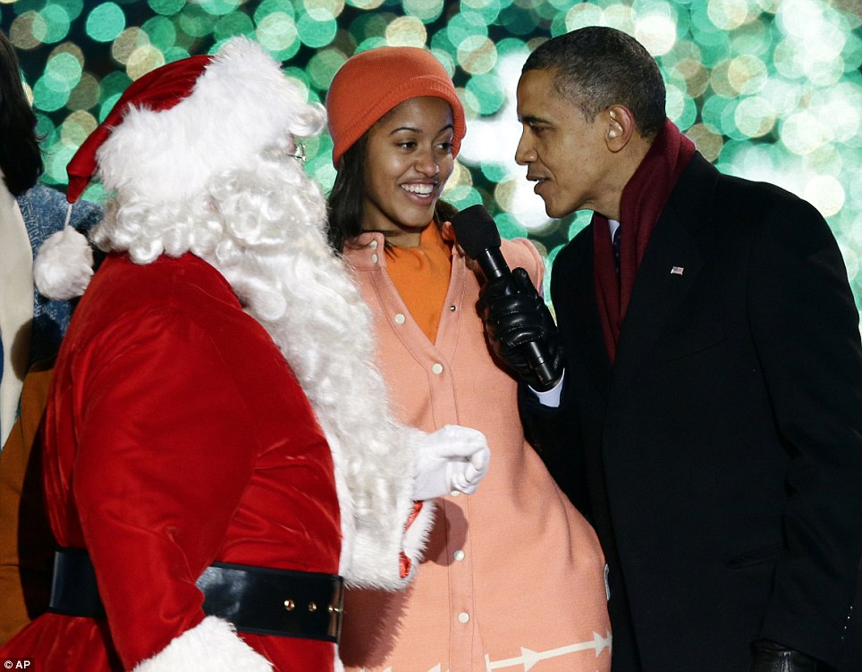 Naughty or nice? President Obama, right, and daughter Malia, sing as Santa Claus arrives