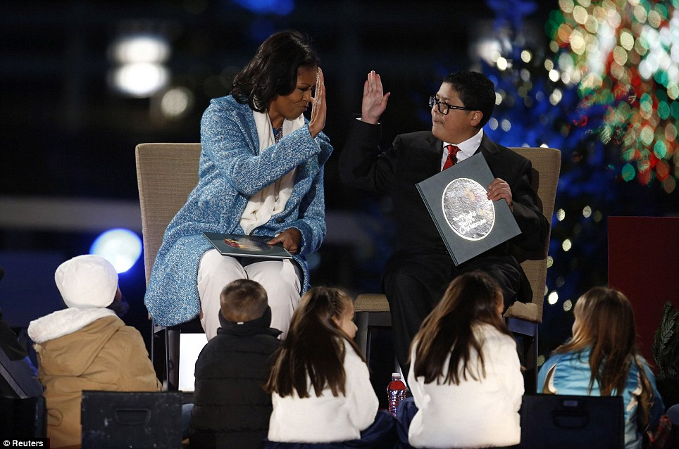 Story time: Mrs O. and actor Rico Rodriguez high-five after reading 'The Night before Christmas' to children