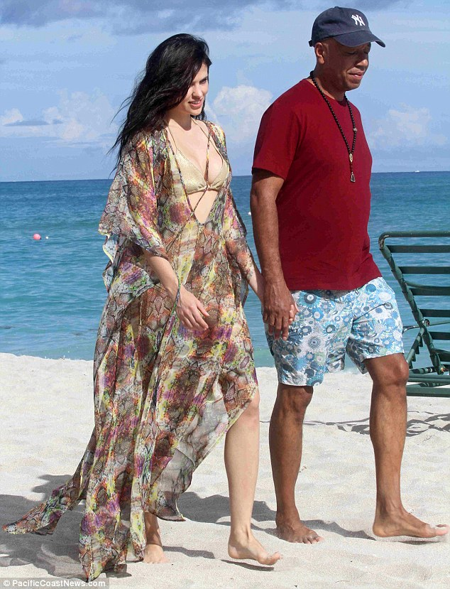 All covered up: Hana wore a kaftan, while Russell wore a shirt, board shorts and a baseball cap